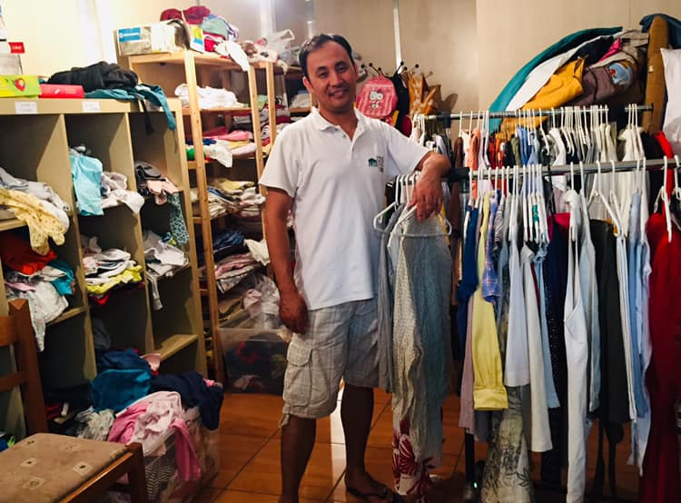 a man stands next to rails of clothes in the CRIBs Free Shop