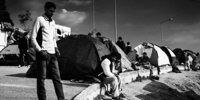 black and whire image of people standing in front of small tents